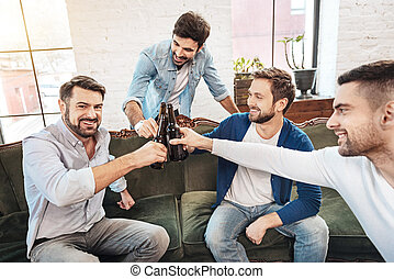 Happy bearded man cheering with his friends - Drinking...
