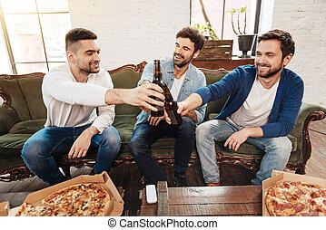 Positive joyful men raising beer bottles for toast - Cheers...
