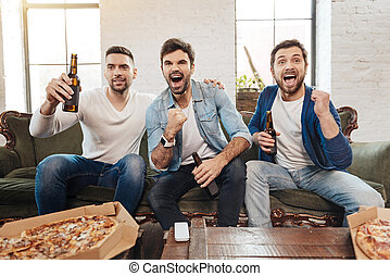 Good looking joyful men cheering for their football team - A...