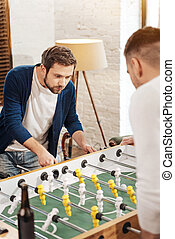 Good looking bearded man playing the table soccer - Intense...