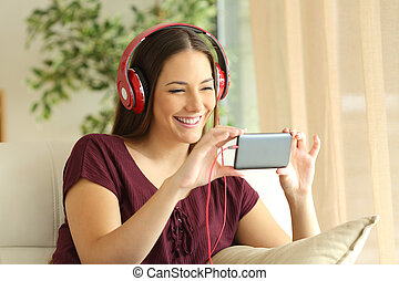 Girl watching videos in a smart phone with headphones -...