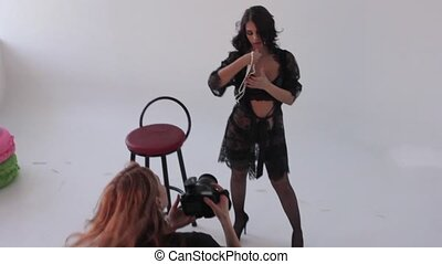 model posing for fashion photographer at fashion photo shoot in studio