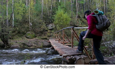 Girl tourist with a backpack goes on a wooden bridge across mountain river