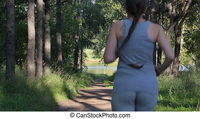 Girl runs along a shady forest green alley. Young woman jogging in the park