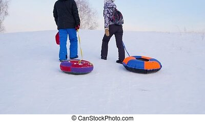 the family rises to snowy hill with snowtube.slow motion. snow winter landscape. Sunset time.