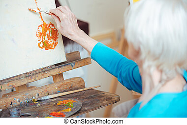 Female artist painting picture with putty knife. - Delicious...
