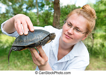 Pretty blond woman holding a turtle - Pretty blond woman in...