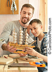father and son with wooden ship, made by hands together