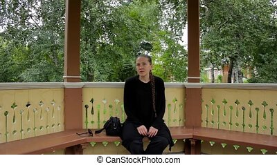 Portrait of a girl with braid dressed in black sitting in the gazebo in summer