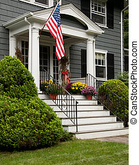U S Flag Hanging off Front Porch with Flowers on Steps - US...