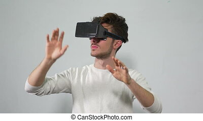 Man wearing virtual reality glasses and making specific...