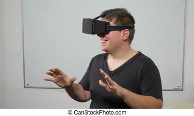 Young man testing virtual reality headset equipment and...