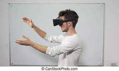 Student trying on VR glasses in classroom a with whiteboard