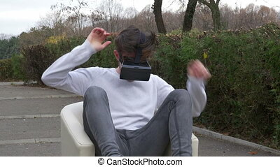 Student sitting in an armchair in a park wearing virtual...