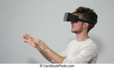 Man with VR headset enters a virtual reality world and...