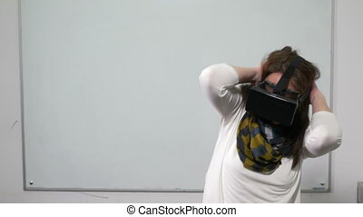 Girl getting scared while playing virtual reality video game with VR glasses during a test session in classroom