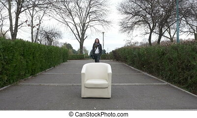 Woman walking into the park finds an armchair on an alley...