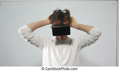 Young man adjusting and trying on virtual reality glasses