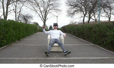 Student sitting relaxed in an armchair in a park wearing...