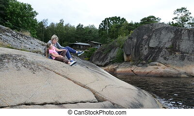 Mother and daughter sitting on the big stones on the sea...