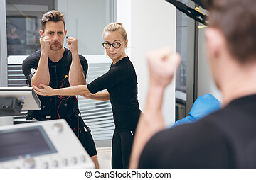 Sportsman teached by personal trainer in front of mirror -...