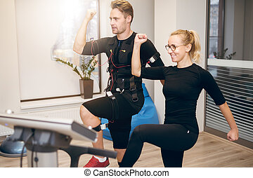 Sportsman doing ems training with personal trainer - Side...