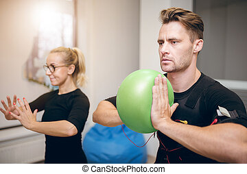 Serious man on ems training with coach at gym - Portrait of...