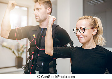 Happy woman training at gym with sportsman - Portrait of...