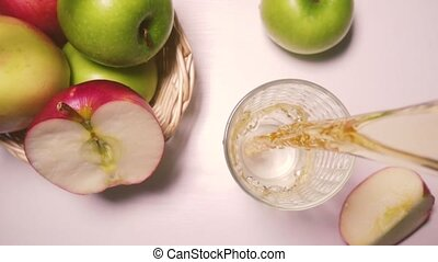Slow motion apple juice is poured into a glass top view -...