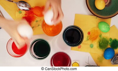 A family painting Easter eggs. Top view - Happy easter! A...