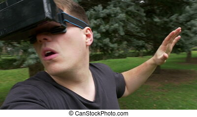 Adult man looking around outdoor through the lens of VR glasses