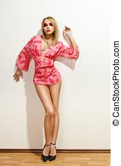 Sexy fashion model posing near wall