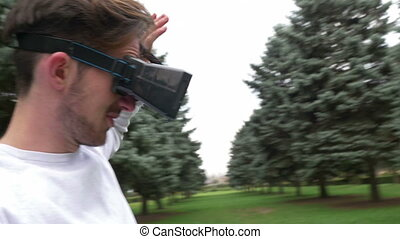 Man wearing virtual reality goggles in park moving and...
