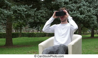 Young man looking around in a virtual reality world using VR glasses and leaves falling on him