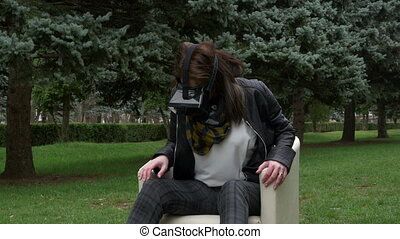 Woman in park using VR headset and smiling and looking at a...