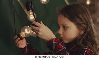 Little girl posing with light bulbs that hang on wires -...