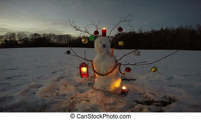 Snowman on january new year evening field with candles, 4K -...
