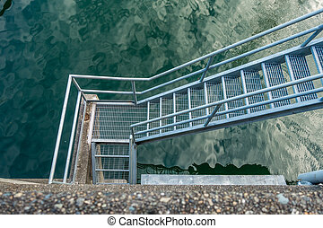 Stairs Over Water - Metal stairs rise up over water.