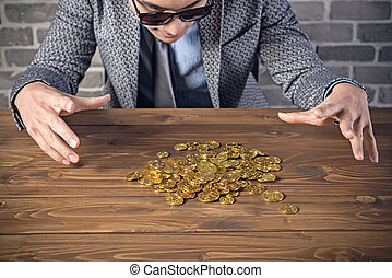 golden coins on the desk - young businessman with golden...