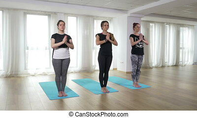 Yoga students doing healthy lifestyle training exercise at...