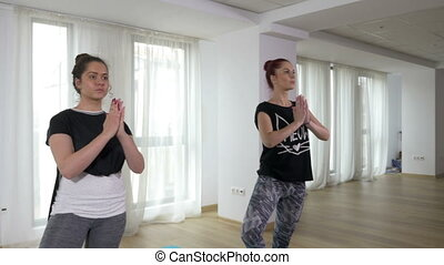 Teenage girls learning yoga with teacher