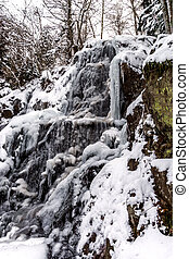 Beautiful icy waterfall in the forest. Vosges mountains....
