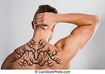 Tattoo On Man's Back - Close-up Of A Man With Tattoo On His...