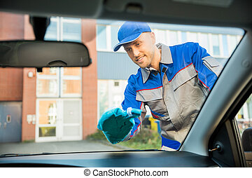 Man Cleaning Car Window With Cloth - Smiling Young Man...