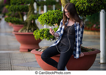 Teen girl using a smart phone and texting sitting in an urban park