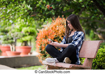 Happy girl using a smart phone in city park sitting on bench