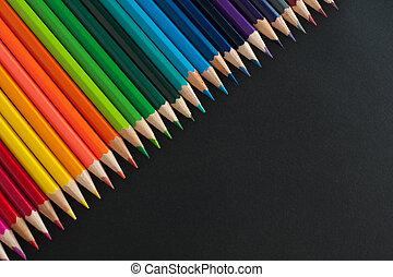 Colour pencils on black texture background
