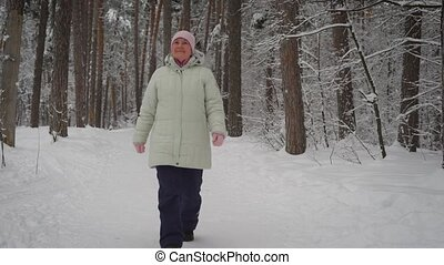 Elderly woman goes on the beaten path in a beautiful...