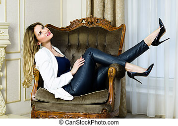 Blonde Girl in leather pants sitting in a couch. Luxury...