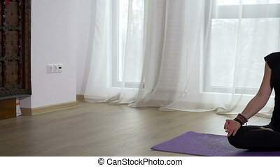 Woman meditating in lotus pose in a yoga studio